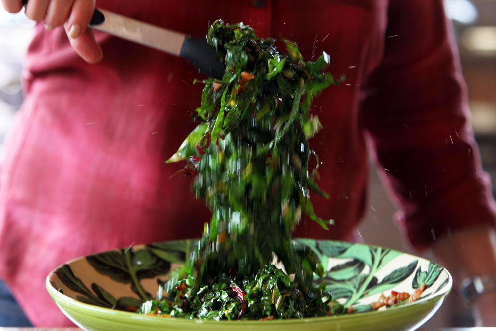 Elizabeth Karmel prepares her Grilled Saute of Garden Greens w/ Smoked Bacon as she and Roger Mooking cook at the Michelson home in Lockhart, TX, as seen on Cooking Channel&#039;s Red, White, and Grill special featuring Williams-Sonoma. (Jennifer Whitney for Cooking Channel)