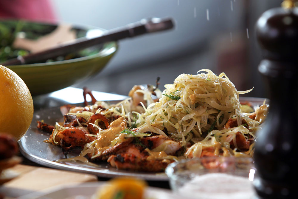 Roger Mooking prepares his Grilled Tandoori Style Octopus w/ Fennel Slaw as he and Elizabeth Karmel cook at the Michelson home in Lockhart, TX, as seen on Cooking Channel&#039;s Red, White, and Grill special featuring Williams-Sonoma. (Jennifer Whitney for Cooking Channel)
