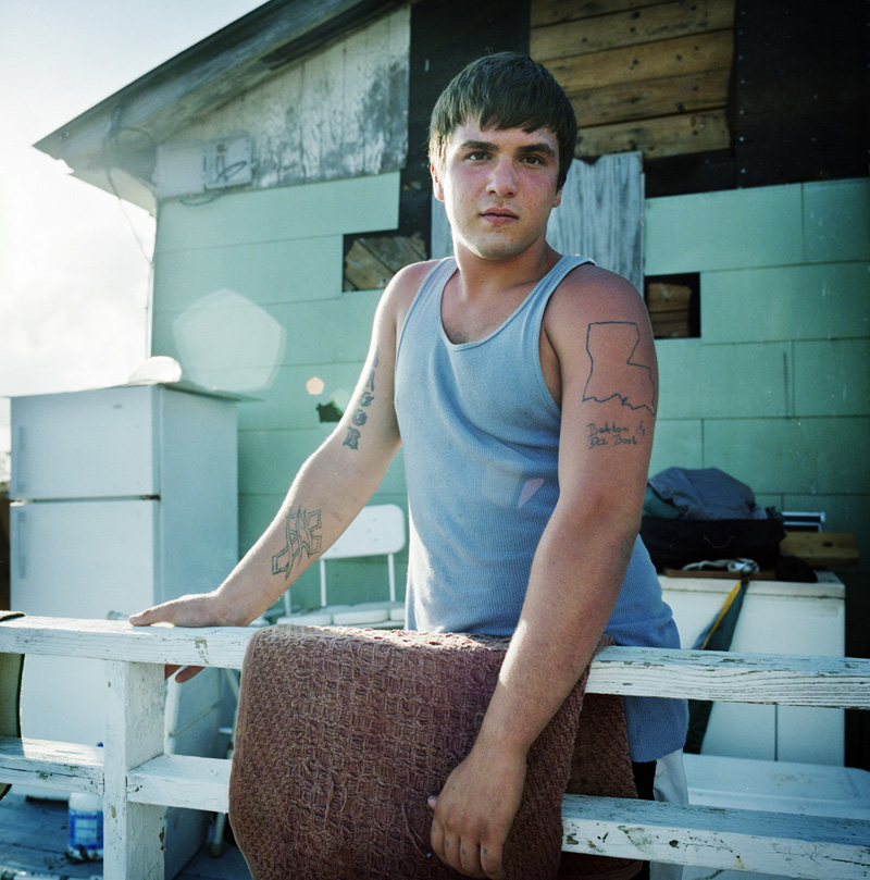 """Jacob Walker shows off his tattoo of Louisiana State and the phrase """"Bottom of the Boot"""" to describe his geographical home on Isle Jean Charles. Walker works on boats that supply off shore oil fields in the Gulf of Mexico. Although the oil industry is largely responsible for severe damage to Louisiana's coastline, it's also the source of income for many residents.  © Kael Alford"""