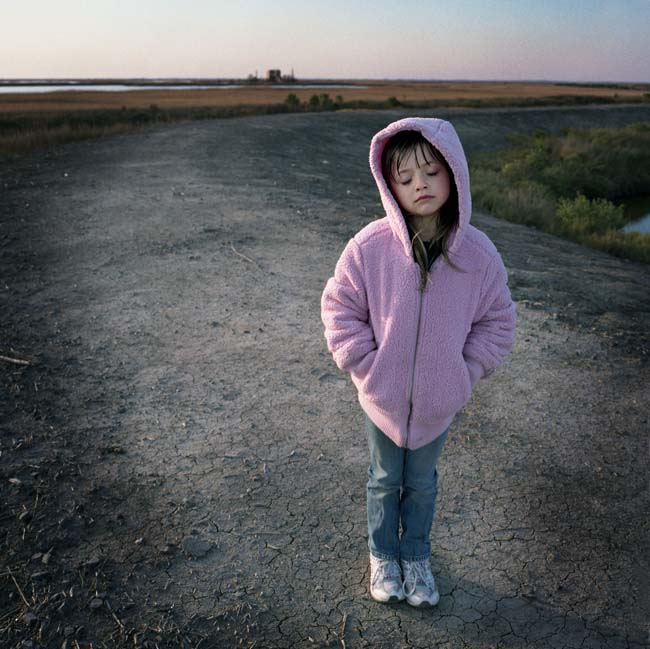 Juliette Brunet stands on the small flood protection levee across the street from her house on Isle Jean Charles. A natural gas pumping station is visible on the horizon. Juliette lost both of her parents when she was younger and is being raised by her uncle who is bound to a wheelchair. Residents of the Island are committed to staying in spite of hardships brought by massive coastal erosion and coastal contamination after the BP oil spill.  Only 70 or so residents remain, down from 300 at it&#039;s peak. Kael Alford 