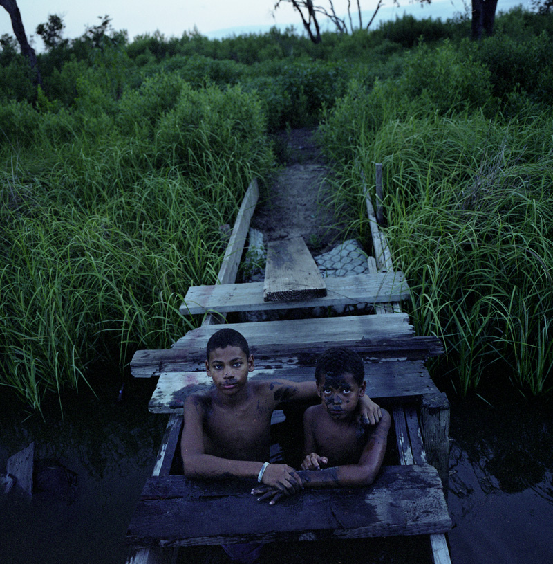 June 2010 Brothers Joseph and Jasmon Jackson stay close to the bridge when they lower themselves into the muddy water of the drainage canal across the street from their house on Island Road on Isle Jean Charles. In the past, most kids swam and played in the waterways and bayous on the Island, but increasingly, parents worry about dangerous trash and contamination found there.  © Kael Alford/Panos Pictures