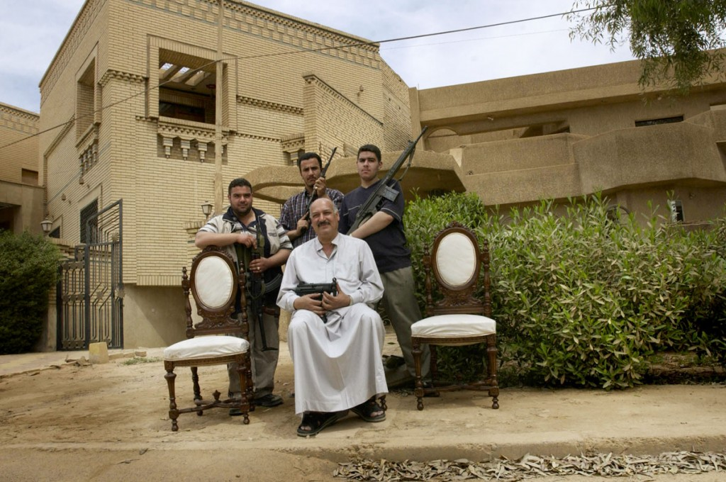 A man with his sons in the wealthy neighborhood of Qasadiya guard their street from looters. The neighborhood has about 20 armed men who patrol 24 hours a day to keep theives at bay who have ransancked the homes of government employees and Hussein family palaces in the area. 12 April 2003  Kael Alford/Panos Pictures