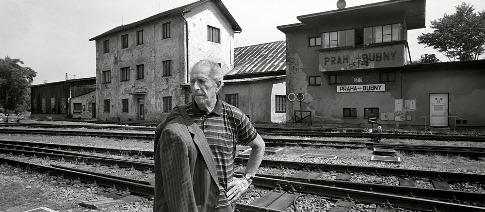 Tommy Karas looks towards his former apartment building, Bubny Rail Yards - Prague, Czech Republic, June 2012. From the vantage point of his fourth floor apartment bordering the Bubny rail yards, nine year-old Tommy Karas regularly watch hundreds of Jews being loaded into rail cars wagons parked on the web of tracks beneath his window.  He was destined to join them two days before the Christmas of 1942.